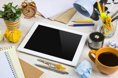 Tablette dans un désordre de travail sur le bureau photos stock