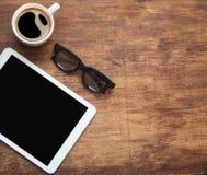 Tablette de Digital avec la tasse de café sur le vieux bureau en bois Pause-café simple d'espace de travail ou L'espace plat de c Photo stock