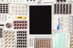 Tablette de Digital entourée par les pilules colorées sur le Tableau Images stock
