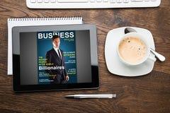 Tablette de Digital montrant la couverture de magazine avec la tasse de thé Images stock