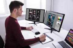 Tablette de Drawing On Graphic de concepteur tout en travaillant sur l'ordinateur photos stock
