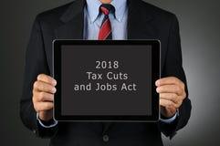 Tablette de participation d'homme d'affaires avec 2018 réductions des impôts et acte des travaux photo libre de droits
