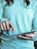 Tablette de participation de femme et doigt d'utilisation Image libre de droits