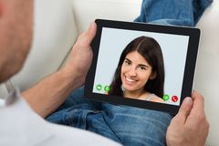 Tablette de Person Videochatting With Woman On Digital Photographie stock