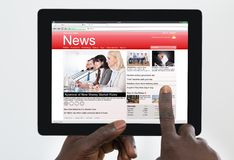 Tablette de Person Watching News On Digital Images libres de droits