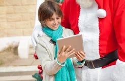 Tablette de Santa Claus And Boy Using Digital Photo stock