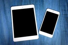 Tablette de tablette avec le téléphone portable sur la table en bois Images stock