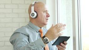 Tablette et écouteurs électroniques d'utilisation d'homme avec la musique de écoute de Bluetooth clips vidéos