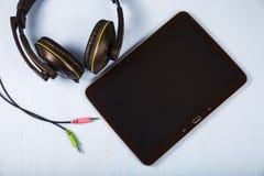 Tablette et écouteurs sur une table en bois bleue Photographie stock