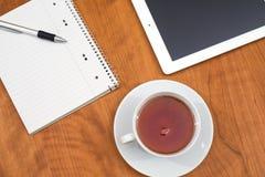Tablette et bloc-notes et une tasse de thé sur la table en bois de l'abov Images libres de droits