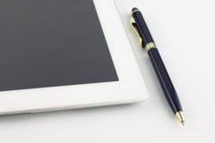 Tablette et un stylo or-bleu en métal moderne sur un fond blanc Images stock