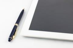 Tablette et un stylo or-bleu en métal moderne sur un fond blanc Photos libres de droits