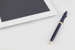 Tablette et un stylo or-bleu en métal moderne sur un fond blanc Photo stock