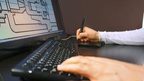 Tablette 28 Fermez-vous de la main d'un ingénieur éditant le plan dans le système de DAO, ligne de rupture sur le moniteur d'affi banque de vidéos