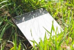 Tablette graphique avec un stylo se situant dans l'herbe épaisse du ressort Photo stock