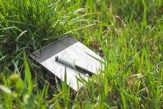 Tablette graphique avec un stylo se situant dans l'herbe épaisse du ressort Photographie stock libre de droits