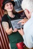 Tablette mûre de signes d'homme au bulletin de paie dans un café Images stock