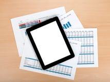 Tablette mit leerem Bildschirm über Papieren mit Zahlen und Diagrammen Lizenzfreie Stockfotografie