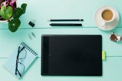 Tablette, ordinateur portable, stylo, verres et tasse avec du café sur la soucoupe sur le fond bleu Image libre de droits