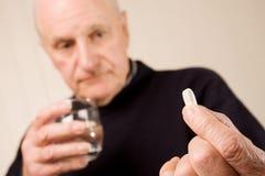 Tablette ou pillule aînée de fixation d'homme plus âgé avec de l'eau Photos libres de droits