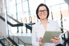 Tablette sûre de Smiling While Using Digital de femme d'affaires photographie stock libre de droits