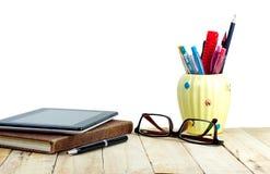 Tablette sur le carnet, les verres, le stylo et la fourniture de bureau bruns Photo stock