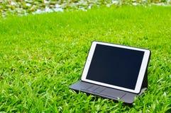 Tablette sur le fond d'herbe verte Photo libre de droits