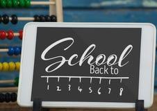 Tablette sur une table d'école avec de nouveau au texte d'école sur l'écran Photo stock