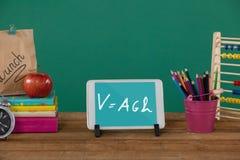 Tablette sur une table d'école avec des icônes d'école sur l'écran Photos stock