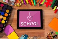 Tablette sur une table d'école avec des icônes d'école sur l'écran Photo libre de droits