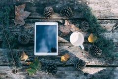 Tablette sur une table en bois avec du café et des pins extérieurs Images libres de droits