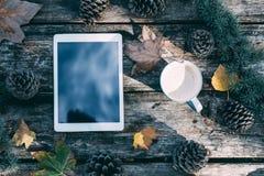 Tablette sur une table en bois avec du café et des pins extérieurs Photo stock