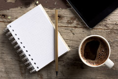 Tablette, téléphone, bloc-notes et café sur la table en bois Photographie stock