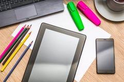 Tablette, téléphone portable, papier, crayons et tasse de café sur la table Images stock