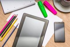 Tablette, téléphone portable, papier, crayons et tasse de café sur la table Image stock
