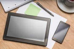 Tablette, téléphone portable, stylo, note et tasse de café sur la table Image libre de droits