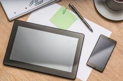 Tablette, téléphone portable, stylo, note et tasse de café sur la table Photos libres de droits
