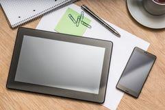 Tablette, téléphone portable, stylo, note et tasse de café sur la table Photographie stock
