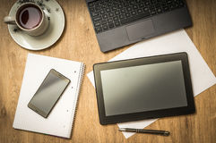 Tablette, téléphone portable, stylo, ordinateur portable et tasse de café sur la table Photo libre de droits