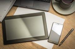 Tablette, téléphone portable, stylo, ordinateur portable et tasse de café sur la table Photographie stock libre de droits