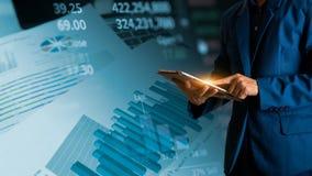 Tablette tactile de doigt d'homme d'affaires avec la courbe de rentabilité de finances et d'opérations bancaires image libre de droits