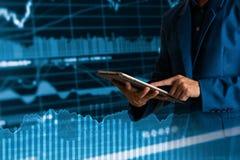 Tablette tactile de doigt d'homme d'affaires avec la courbe de rentabilité de finances et d'opérations bancaires photos stock