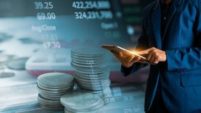 Tablette tactile de doigt d'homme d'affaires avec la courbe de rentabilité de finances et d'opérations bancaires des actions image stock