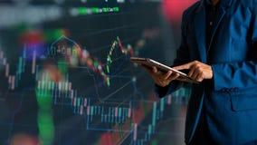Tablette tactile de doigt d'homme d'affaires avec la courbe de rentabilité de finances et d'opérations bancaires des actions image libre de droits