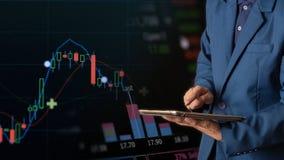 Tablette tactile de doigt d'homme d'affaires avec la courbe de rentabilité de finances et d'opérations bancaires des actions photographie stock libre de droits