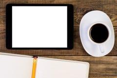 Tablette, tasse de café et carnet sur le bureau Photos libres de droits