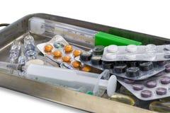 Tabletten, ampullen voor injectie, spuiten en een thermometer totreat een patiënt Stock Foto's