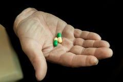 Tabletten in de hand van een bejaarde stock fotografie