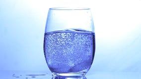 Tabletten die in een Glas Water tegen Blauwe Achtergrond vallen, stock video