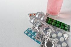 Tabletten op een lichte achtergrond Verschillende types van pillen Oplosbare tablet in een glas water Gesloten pillen in pak stock afbeelding